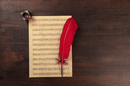 An overhead photo of a piece of sheet music, shot from the top on a dark rustic wooden background with a quill and an ink well, with a place for text