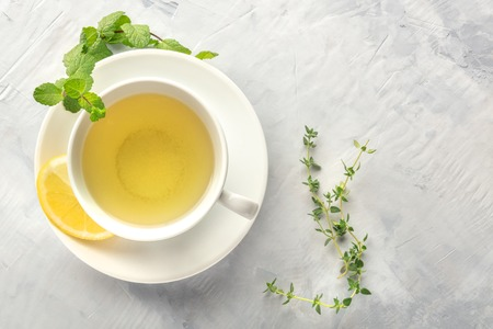A cup of green tea with lemon, shot from above with mint, thyme, and copy space