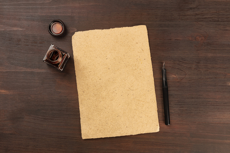 A vintage background with old parchment paper, a nib pen and an ink well, shot from above on a dark wooden background with a place for text