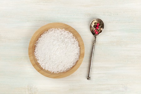 A bowl of sea salt and a spoon with pepper, shot from above on a white wooden background with copy space