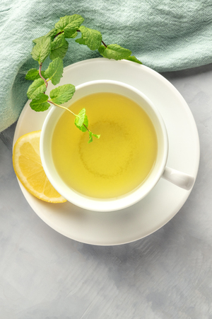 A cup of green tea with lemon and mint leaves, shot from above on an abstract grey background with copy space
