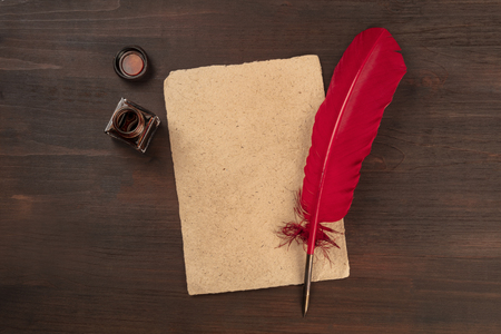 A vintage background with a quill pen on a piece of old parchment paper, with an ink well, shot from the top on a dark wooden background with copy space Stock Photo