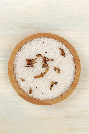 A bowl of sea salt infused with truffle shavings, shot from above with a place for text