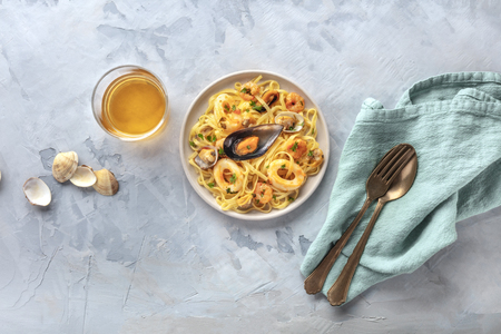 Seafood pasta. Tagliolini with mussels, shrimps, clams and squid rings, shot from the top with a glass of white wine and a place for text