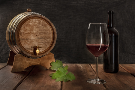 A glass of red wine with a bottle, a wine barrel, and vine leaves, side view on a dark rustic background, low key photo with a place for text