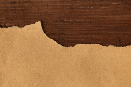 An overhead photo of torn brown kraft paper on a dark rustic wooden background, a grunge design template with copy space