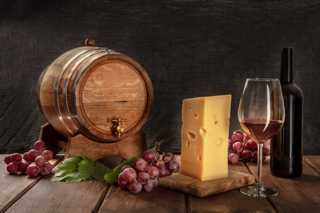 A glass of red wine with a bottle, a wine barrel, a large piece of cheesse, grapes, and vine leaves, side view on a dark rustic background, low key photo with a place for text