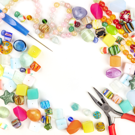 A square photo of beads with tools for making jewelry, shot from above on a white background with copyspace