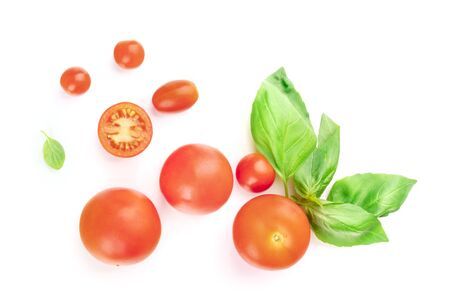 A closeup photo of cherry tomatoes and basil leaves, shot from above on a white background with copy space