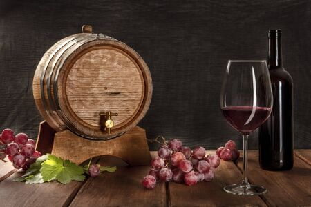 A glass of red wine with a bottle, a wine barrel, grapes, and vine leaves, on a dark rustic background, low key photo with a place for text
