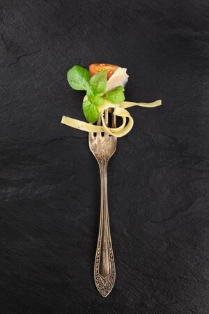 Italian pasta. A vintage fork with pappardelle, basil, cheese, cherry tomato, and pepper, shot from above on a black background with a place for text