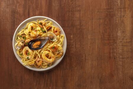 Seafood pasta. A plate of tagliolini with mussels, shrimps, clams and calamari rings, shot from above on a rustic wooden background with a place for text Фото со стока