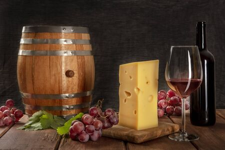 A glass of red wine with a bottle, a wine barrel, a large piece of cheesse, grapes, and vine leaves, on a dark rustic background, low key photo with copy space
