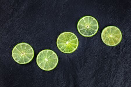 Lime slices, shot from above on a black background with copy space