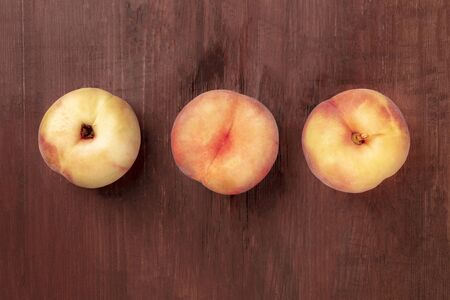 Vibrant organic flat saturn peaches, shot from above on a dark rustic wooden background with a place for text
