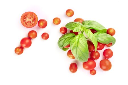 Cherry tomatoes and fresh basil leaves, shot from the top on a white background with a place for text