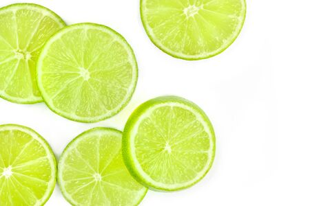 A closeup of vibrant lime slices, shot from the top on a white background with a place for text Stock Photo