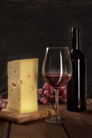 A glass of red wine with a bottle, a large piece of cheesse, and grapes on a dark rustic background, low key photo with a place for text