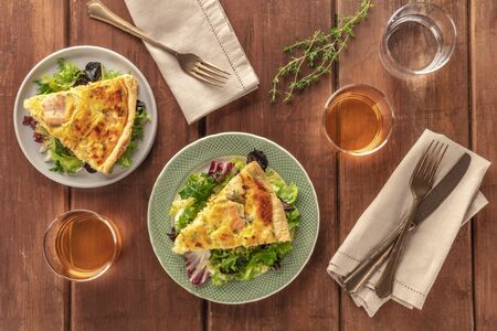 Slices of French quiche with salmon, with green salad leaves, thyme and white wine, shot from the top on a dark rustic wooden background Фото со стока