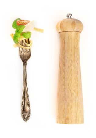 Italian pasta design elements. A fork with pappardelle, basil, cheese, and tomato, shot from above on a white background with a pepper mill and copy space