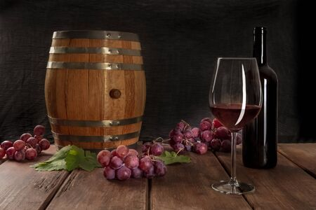 A glass of red wine with a bottle, a wine barrel, grapes, and vine leaves, on a dark rustic background, low key photo with copy space Фото со стока