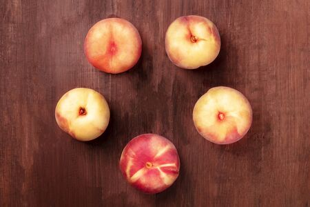 Vibrant organic flat saturn peaches, shot from the top on a dark rustic wooden background forming a circle for copy space