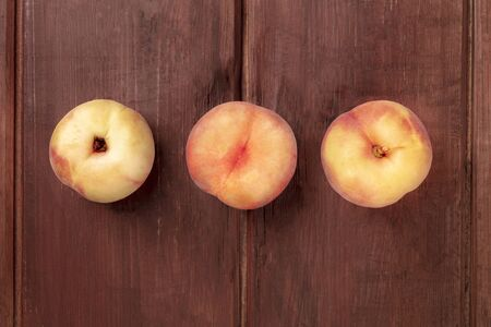 An overhead photo of vibrant organic flat saturn peaches on a dark rustic wooden background with copy space