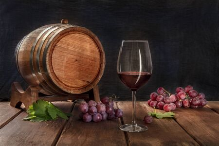 A glass of red wine with a wine barrel, grapes, and vine leaves, on a dark rustic background, low key photo with a place for text