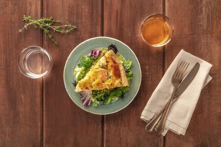 A slice of a French quiche with salmon, with green salad leaves, thyme and white wine, shot from above on a dark rustic wooden background