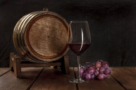 A glass of red wine with a wine barrel and grapes on a dark rustic background, low key photo with copyspace