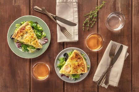 Slices of a French quiche with salmon, with green salad leaves, thyme and white wine, shot from above on a dark rustic wooden background
