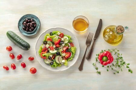 Greek salad with ingredients. An overhead photo of a plate of fresh salad with lettuce, feta cheese, tomatoes, cucumbers, onions and olives. A dinner with white wine Фото со стока