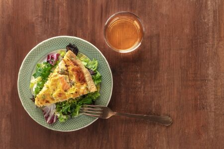 A slice of a French quiche with salmon, with green salad leaves, and white wine, shot from above on a dark rustic wooden background with copyspace