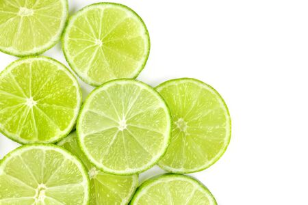 Vibrant lime slices, shot from above on a white background with copy space