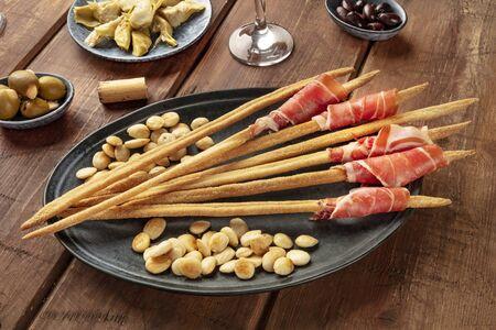 Italian antipasti. Grissini with parma ham