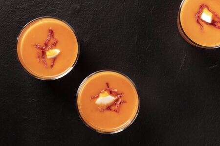 Salmorejo, Spanish cold tomato and bread soup, in glasses, shot from the top on a black background