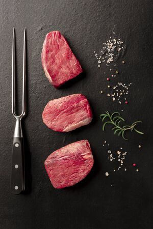 Raw beef steaks with salt, pepper, rosemary, and a carving fork on a black background 写真素材