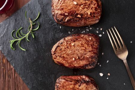Beef steaks with salt, rosemary, and red wine, close-up overhead shot with a place for text 写真素材