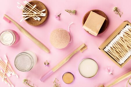 Plastic-free, zero waste cosmetics, flat lay on a pink background. Bamboo toothbrushes and cotton swabs, konjac sponge, natural organic products