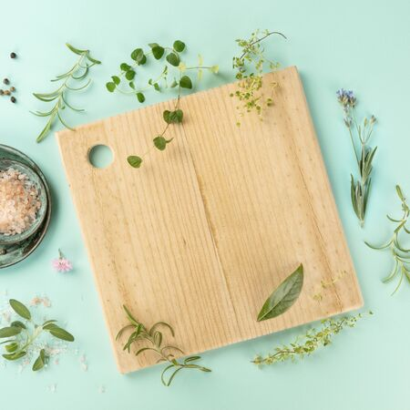Cooking Design Template. Cutting board with herbs, salt, and pepper, shot from above on a teal background with copy space