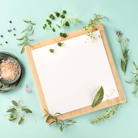 Cooking Design Template. A clipboard with herbs, salt, and pepper, shot from above on a teal background with a place for text, square frame