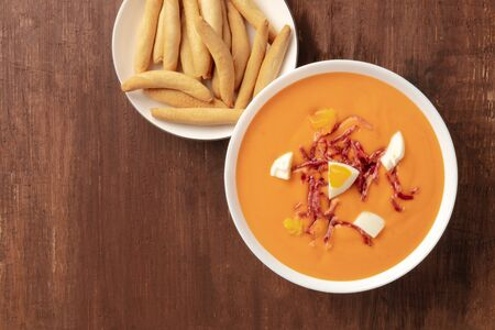 Salmorejo, Spanish cold tomato soup, shot from the top on a dark rustic wooden background with picos, typical breadsticks, and a place for text