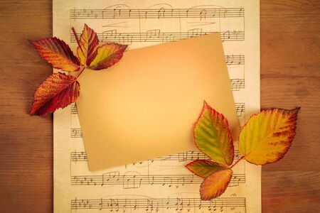 Autumn background with vibrant fall leaves with a card and sheet music, a design template for a flyer, invitation, or gift card with a place for text and logo