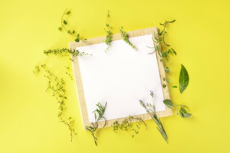 Recipe Design Template. A clipboard with aromatic cooking herbs, shot from the top on a yellow background with copy space Stock Photo