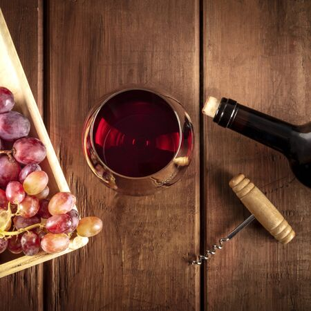 Weinprobe. Ein Foto von einem Rotweinglas mit einer Flasche, Trauben und einem Vintage-Korkenzieher, Overhead-Quadrataufnahme auf einem dunklen rustikalen Holzhintergrund Standard-Bild