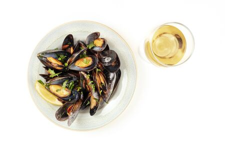 Marinara mussels, moules mariniere, shot from the top on a white background with a glass of wine and copy space