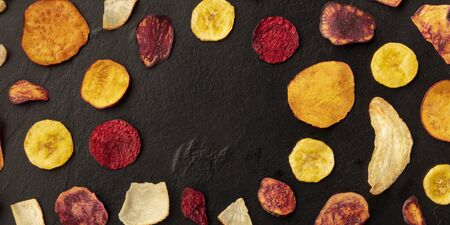 A panorama of dry fruit and vegetable chips, healthy vegan snack, an organic food flat lay pattern on a black background, forming a frame with a place for text Foto de archivo