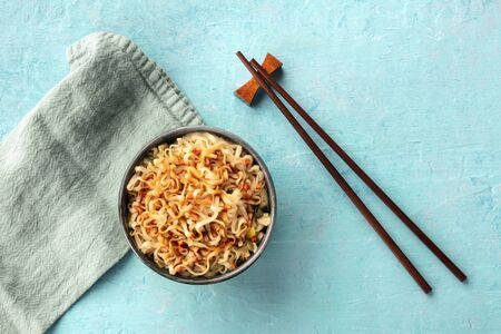 Instant ramen noodles with carrot and a sauce, shot from the top on a teal blue background with chopsticks and a place for text Banco de Imagens