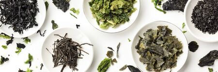 A panorama of dry seaweed, sea vegetables, overhead shot on a white background