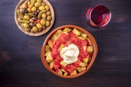 Patatas bravas, Spanish potatoes, with a glass of wine and olives, shot from the top on a dark background with a place for text 免版税图像